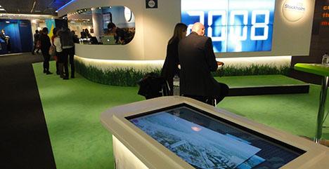 Två stora liggande touch-skärmar visar på ett utmärkt sätt några större projekt i Stockholm. Men då krävs det att fler än svenskarna hittar skärmarna.