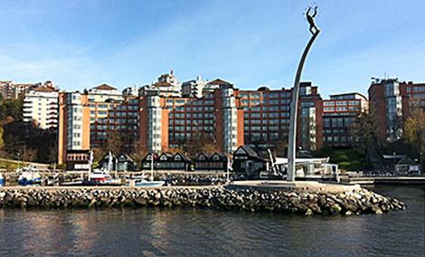 """Vy från vattnet. I fonden syns kontorshuset vid Augustendalsvägen som föreslås bli bostäder. Till höger om """"Gud Fader på himmelsbågen"""" skymtar kajen och bergbanan. Bild: Nacka kommun."""