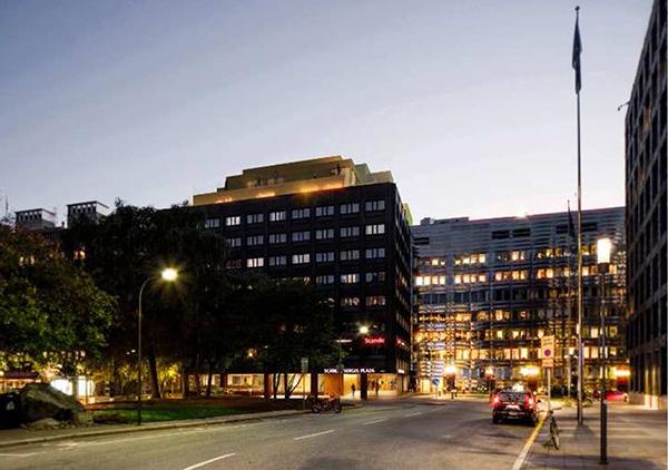 Vy mot hotellet från Brunkebergstorgs norra hörn med Riksbanken till höger och stadsteatern i fonden. Bilden visar påbyggnaden på taket samt den ljussatta arkaden och hotellentrén. Illustration: Wingårdh Arkitektkontor.